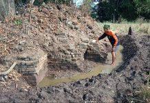 Warga membersihkan tanah pada struktur batu