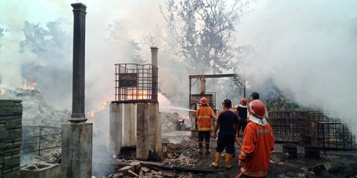 Petugas PMK tengah berusaha memadamkan kobaran api di pabrik pakan ternak.